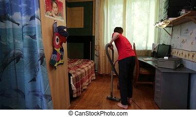 Teen boy vacuuming the floor in the room