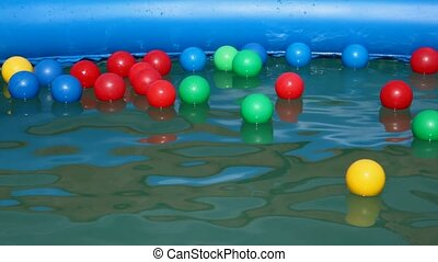 boy swimming after colorful balls