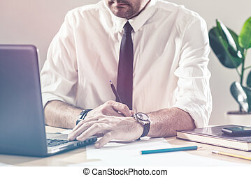 Businessman writing notes and using laptop at office desk -...