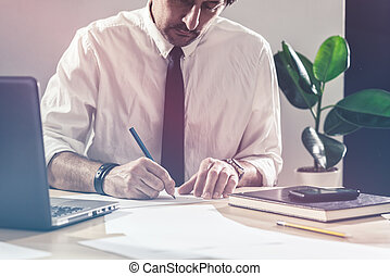 Businessman sketching business diagram at office desk -...