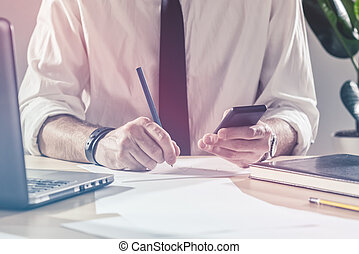 Businessman writing notes from mobile phone at office desk -...