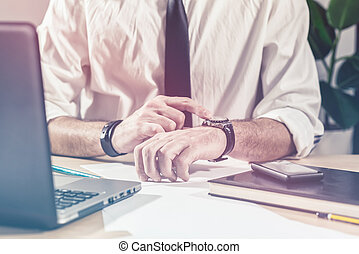 Businessman checking time on watch at office desk -...