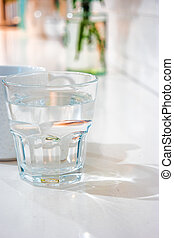 The glass of cool fresh wter on the table in living room -...