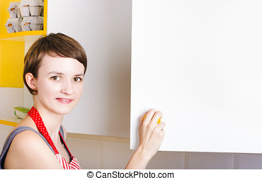Woman searching kitchen cupboard for ingredients - Cute...