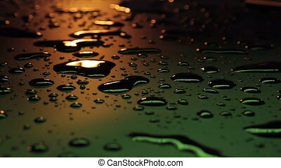 Water drops on black with the lights reflecting
