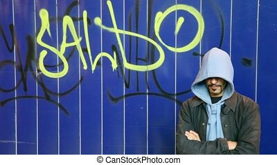 man standing against wall with graffiti