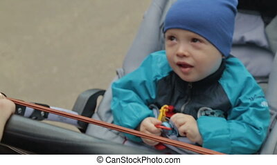 Child is sitting in a carriage and talking, Slowmotion