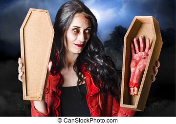 Female Halloween zombie holding undead hand