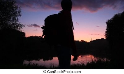 traveller with rucksack looks at sunset lake and lifts hands