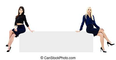 Two businesswomen showing an empty board,lots of copyspace