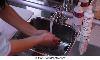 A Woman Washes Her Hands With Soap And Water - A woman...