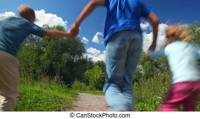 father with son and daughter running in park, join hands, from camera