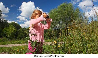 little girl photographs flower outdoor