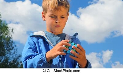 portrait of boy solves earth cube in park