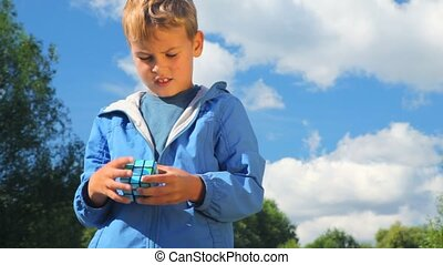 boy solves earth cube in park