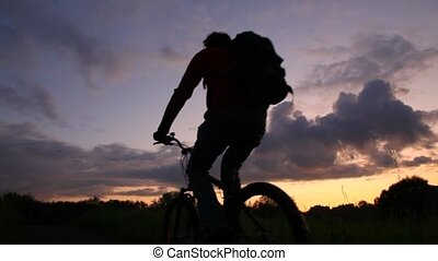 boy and man riding bicycles on sunset background, from camera