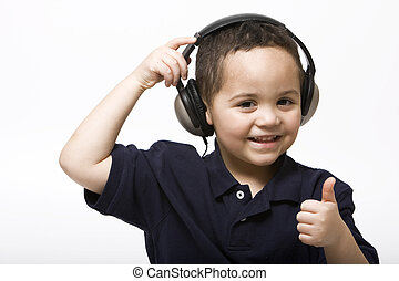 Boy giving thumbs up - Young boy removing headphones giving...