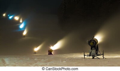 Lots of the snow cannons working at night on a ski slope...