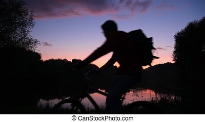 man with rucksack on bicycle looks at sunset lake
