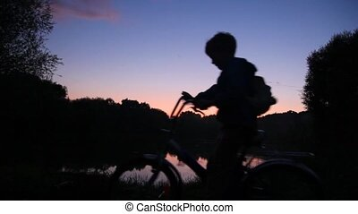 boy with rucksack on bicycle looks at sunset lake