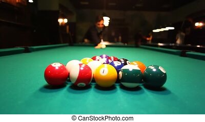 man in billiards breaks balls