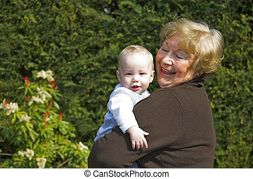 Grandma and grandson - Happy grandmother holding grandson in...