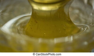 Honey drips in jar on the table - honey drips from the spoon...