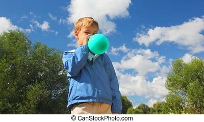 boy inflating blue balloon in park