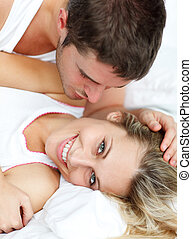 Cheerful man looking at his girlfrined lying in bed