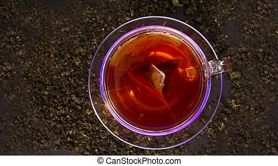 Cup of tea rotation on the black background