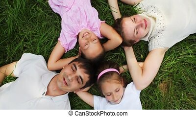 family with two little girls lies on lawn