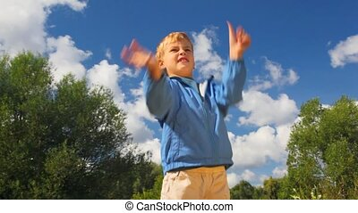boy throwing up blue balloon in park
