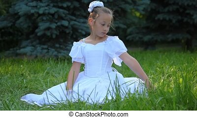girl in white dress sits on grass and touches it with her hand