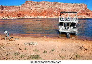 Anchors Away - Vacationers prepare houseboat for overnight...