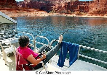 Enjoying Fishing Lake Powell - Woman fishes and enjoys view...