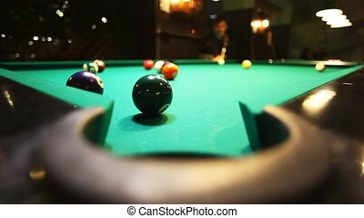 man in billiards shoots green ball in pocket