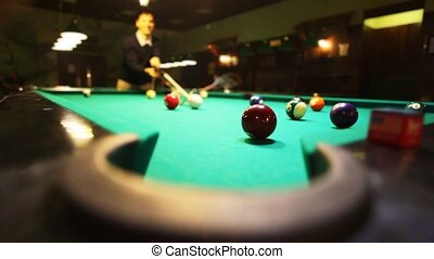 man in billiards shoots red ball in pocket