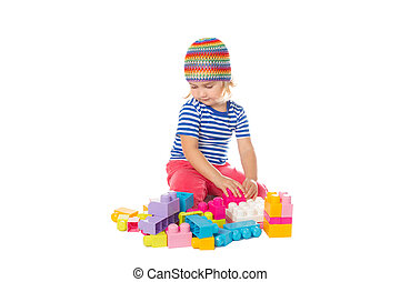 Little girl in a colorful shirt playing with construction toy blocks building a tower.