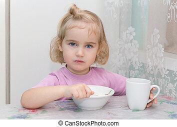 Little girl eats porridge from sitting at the table - Little...