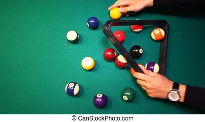 hands collect balls in triangle on biliards table