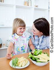 Radiant little girl eating vegetables with her mother in the kitchen