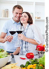 Smiling couple drinking wine while cooking