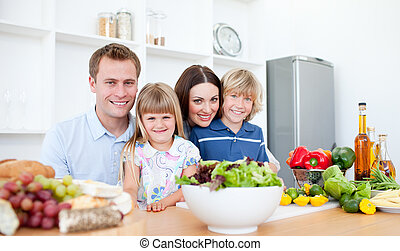 Smiling parents and their children preparing dinner together...