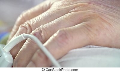 Pulse oximeter sensor at senior patient's finger - Pulse...
