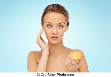 young woman applying cream to her face - beauty, people,...