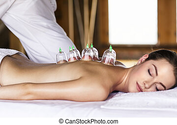 Woman with cupping treatment on back - Woman laying on chest...