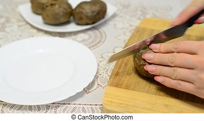 Woman cuts a hot baked potato - A Woman cuts a hot baked...