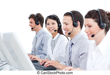 Multi-cultural customer service agents working in a call...