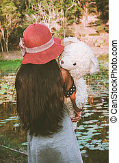 asian cute girl standing alone at the lagoon and hand bear hug,vintage tone