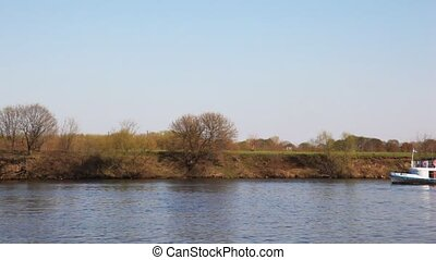 ship swims on the river against trees